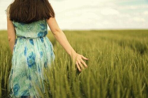 nainen kulkee viljapellossa