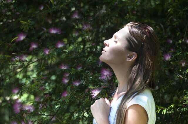 nainen koittaa hengitysharjoitusta puun alla