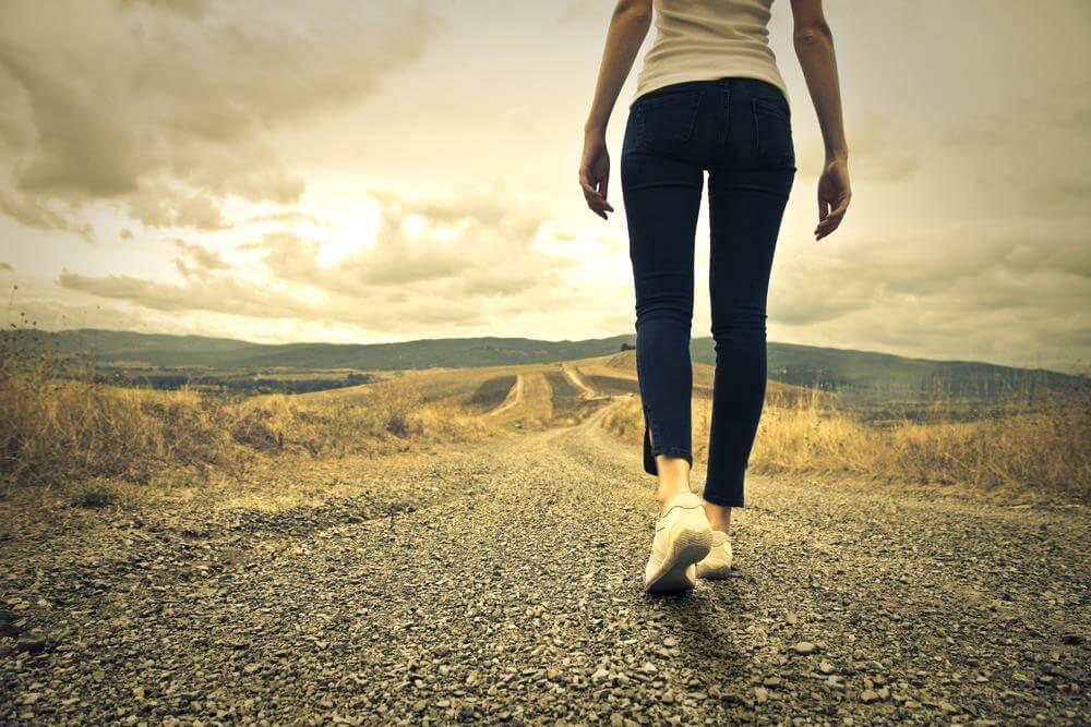 nainen kävelee pitkällä polulla