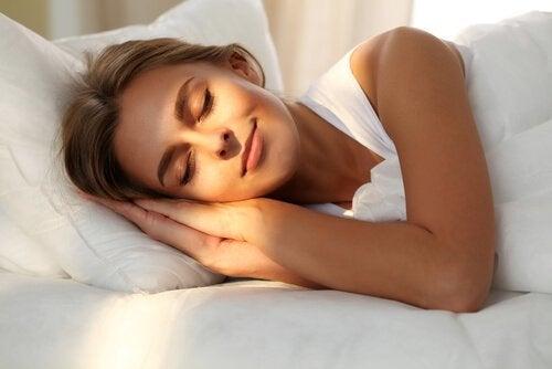 nainen hymyilee aamulla sängyssä