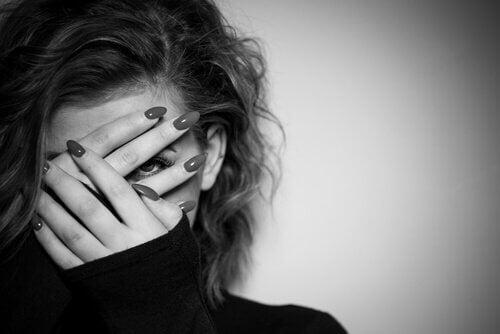 nainen laittaa kädet silmillensä