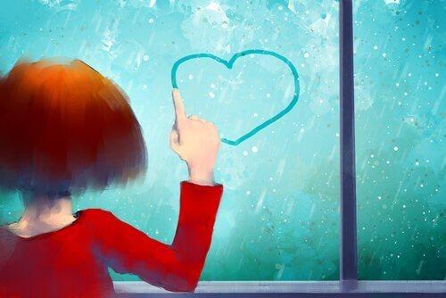 tyttö piirtää sydämen ikkunaan