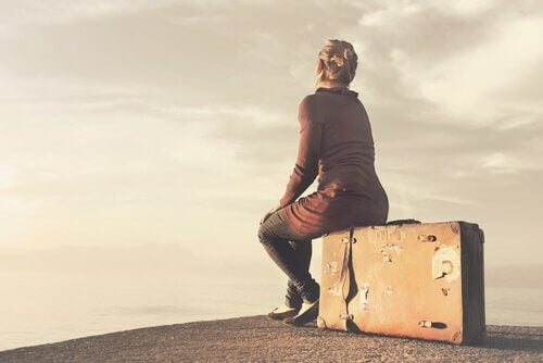nainen istuu matkalaukun päällä