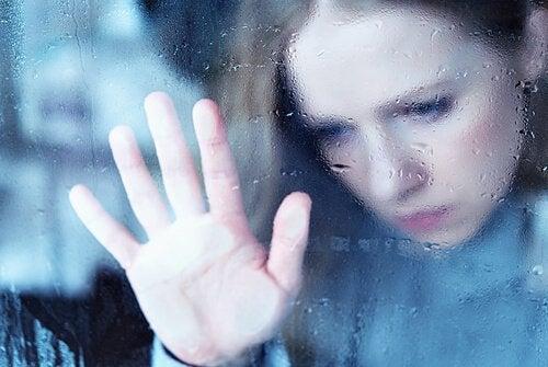 nainen huuruisen ikkunan takana