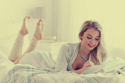 nainen kirjoittaa päiväkirjaansa sängyssä