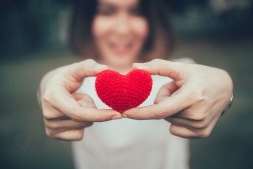 nainen pitelee pientä sydäntä käsissään