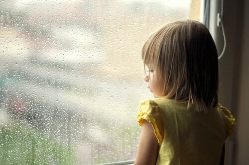 pieni tyttö katselee sateisen ikkunan läpi