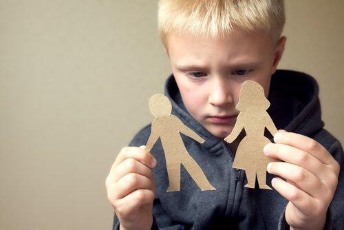 poika pitelee käsissään äidin ja isän muotoisia paperinukkeja