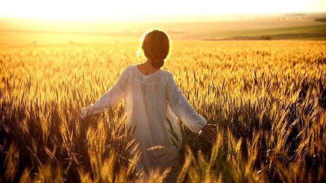 nainen aurinkoisessa viljapellossa