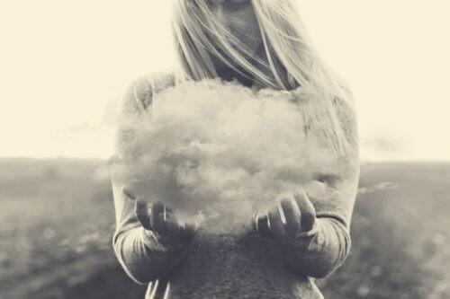 nainen pitelee pilveä käsissään