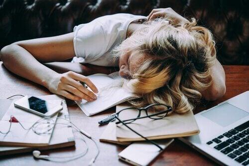 väsähtänyt nainen työpöydällään
