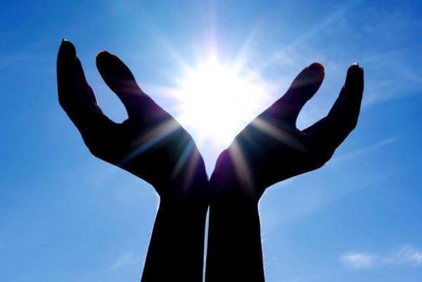 kädet pitelevät aurinkoa