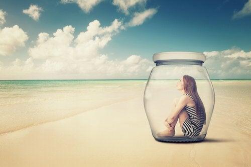 nainen lasipullossa rannalla