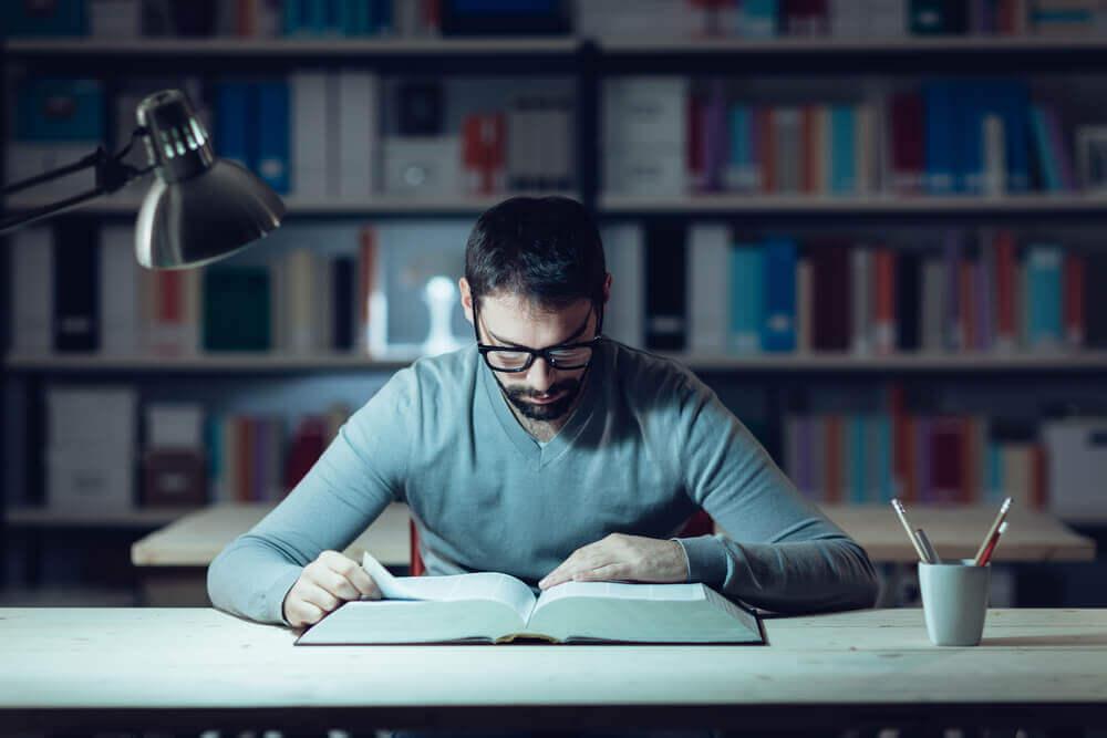 mies lukee kirjastossa