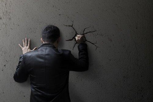 itsetuhoisa henkilö lyö nyrkkinsä seinään