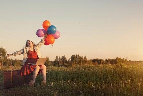 iloinen nainen ilmapallot kädessä