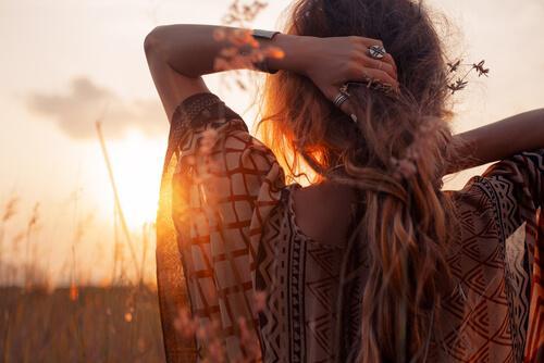 nainen nauttii auringonlaskusta