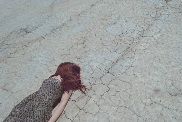 nainen makaa kuivalla maalla