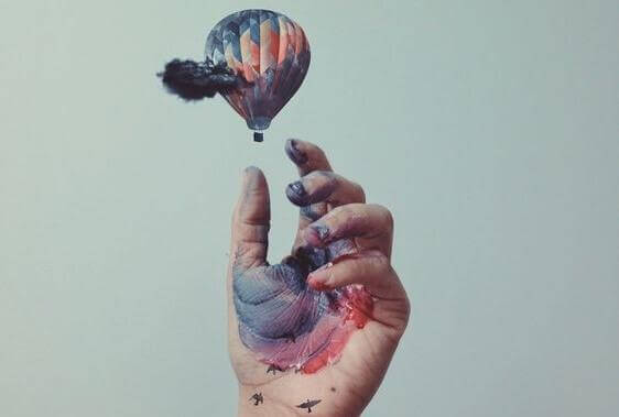 kädessä maalia ja käsi tavoittelee kuumailmapalloa