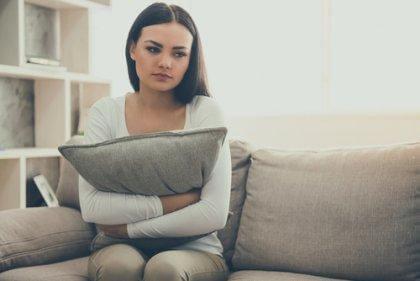 nainen halaa tyynyä sohvalla