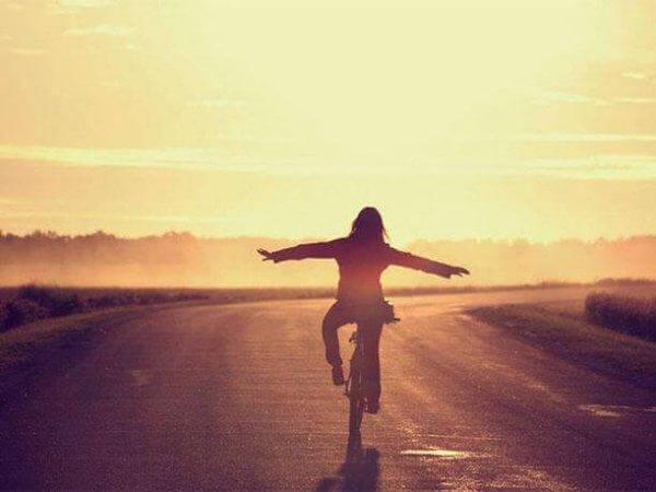 tyttö ajaa pyörää ilman käsiä