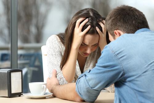 epätoivoinen nainen ja mies lohduttaa