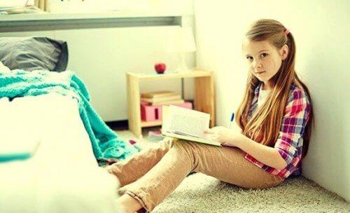 perheen ainoana lapsena tyttö on yksin huoneessaan lukemassa kirjaa
