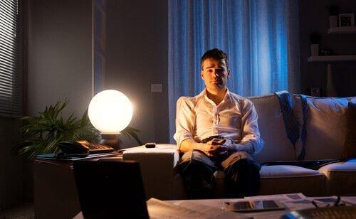 mies istuu sohvalla keskellä yötä