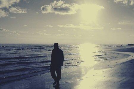 mies kävelee yksin rannalla