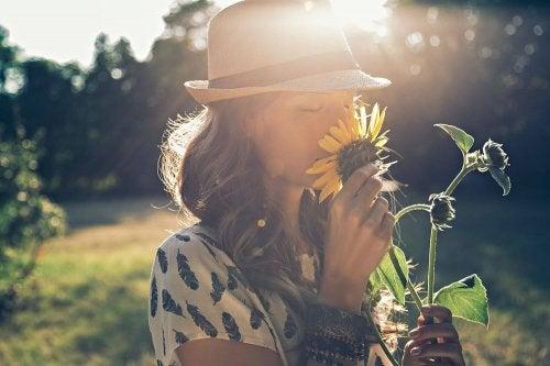 Itsensä irrottaminen maailmasta: nainen haistaa kukkaa
