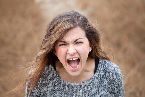 nainen huutaa ja hänellä on maalia kasvoissaan