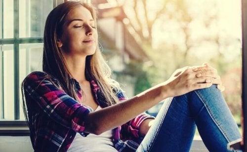 nainen meditoi ikkunan edessä