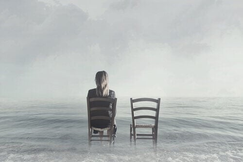 Nainen istuu tuolissa vedessä