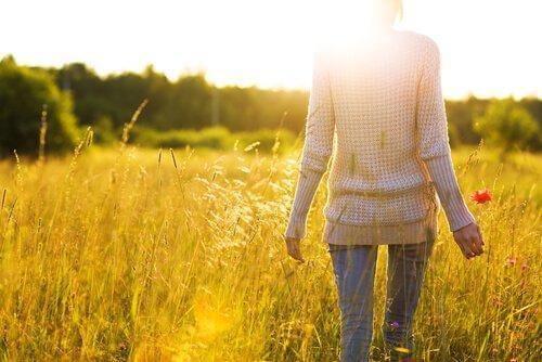 nainen kävelee pellolla
