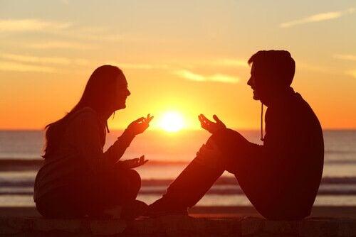 pariskunta keskustelee rannalla
