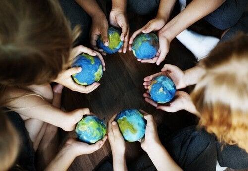 lapsilla käsissään pikku Maapallot