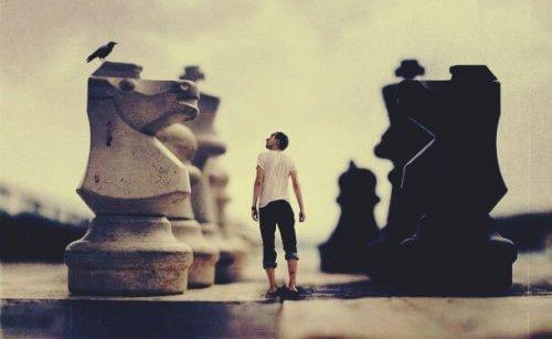 mies ja jättimäiset shakkinappulat
