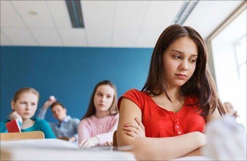 tyttö mököttää koulussa