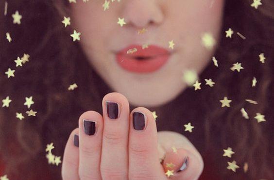nainen puhaltaa tähtiä
