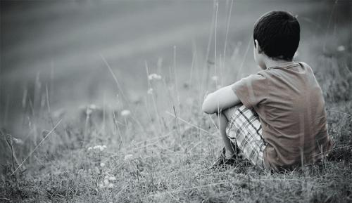 yksinäinen poika nurmikolla
