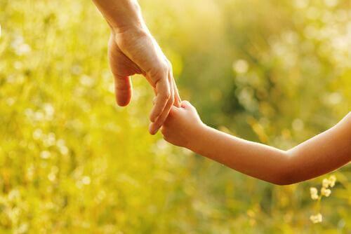 aikuinen pitää lasta kädestä