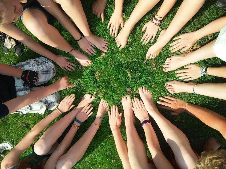 ryhmä ihmisiä hyväilee nurmikkoa