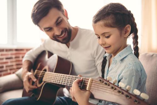 isä opettaa tytärtään soittamaan kitaraa, mutta tekeekö musiikki lapsista älykkäämpiä?