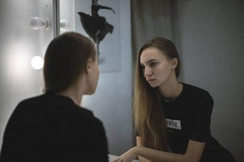 Minäkuva: nainen katsoo peiliin
