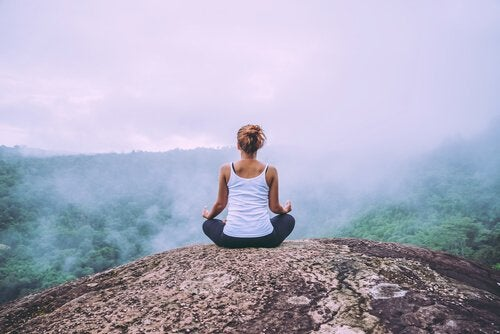 nainen meditoi vuorella