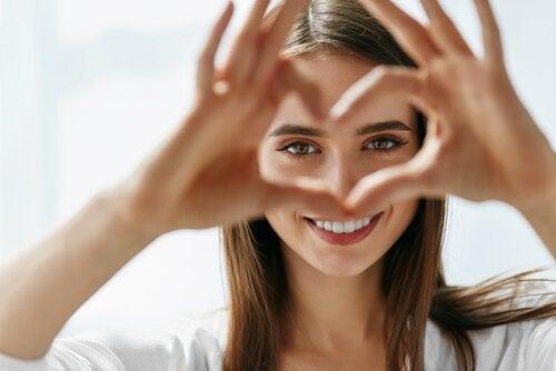 nainen tekee sydämen sormillaan