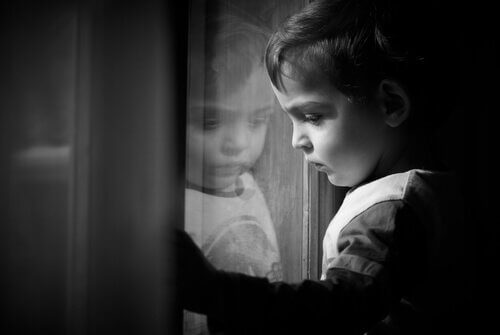 pieni poika katselee ikkunasta ulos