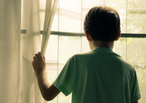 Älyllinen vajavaisuus: lapsi katsoo ulos ikkunasta