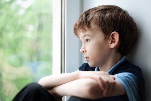 Kiusaamisen terveysvaikutukset: poika katsoo ikkunasta