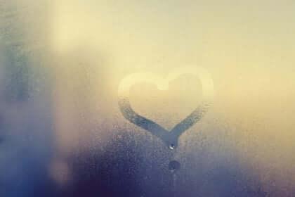 Sydän piirrettynä huurteiseen lasiin.